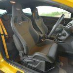 いかにも高価そうなレカロ製のセミバケットシート。座面もサイドサポートも硬く、いかにもレーシーだが、シートバックの角度調整や後席へのエントリーのため、ワンタッチでシートバックを倒すことができる(当たり前か)。シートベルトはイエロー!
